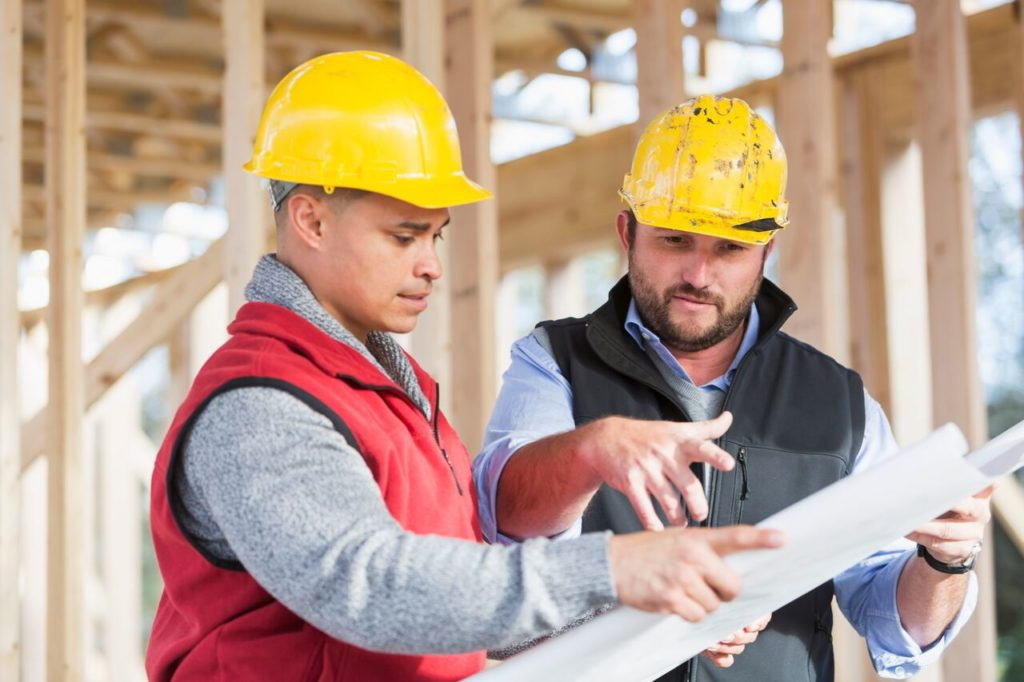 Construction contractor and a builder discussing the construction plan to prevent Sydney building disputes   Contracts Specialist